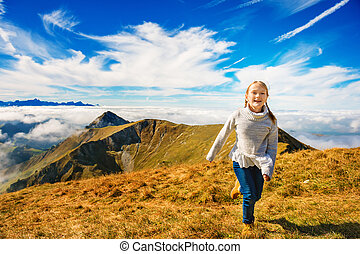 Portrait of a cute little girl in mountains, wearing grey...