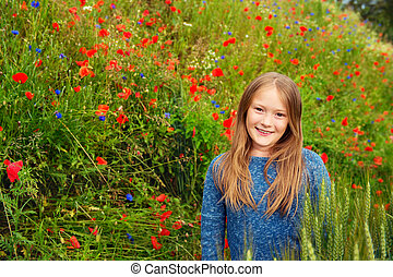 Outdoor portrait of adorable little blond girl of 8-9 years...