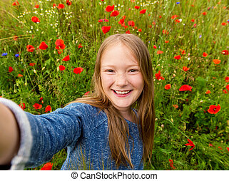 Funny little girl doing selfie in poppy field Preteen 8-9...
