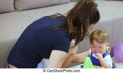 Mother comforting crying baby - On floor crying child...