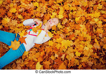 Autumn portrait of a cute little girl of 8-9 years old,...
