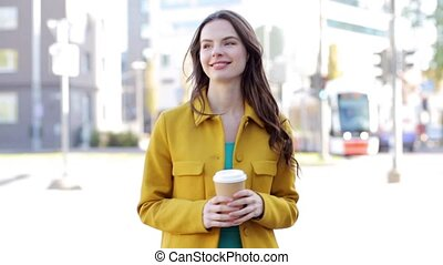 happy young woman drinking coffee on city street - drinks...