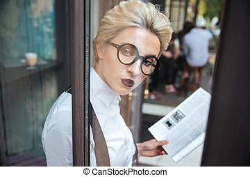 Beautiful young stylish woman reading book in cafe wearing...