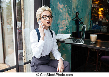 Businesswoman working in a cafe - Candid image of a...