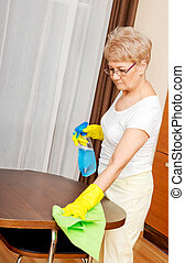 Elderly woman in yellow gloves cleaning table