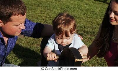 Parents kiss child outdoors - Nature Parents kissing child...