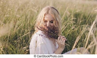portrait of a woman smelling a lavender flower