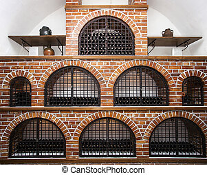 Wine cellar brick vault - Old bottles of wine maturing in a...