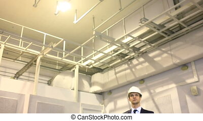 man in business suit and helmet inspects premises consults...