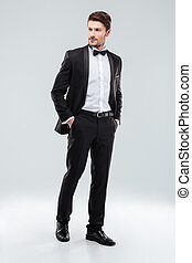 Full length of confident attractive young man in tuxedo