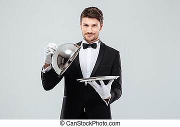 Happy young waiter lifting metal cloche from serving tray -...