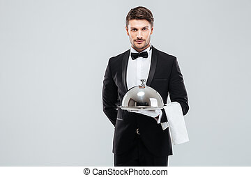 Waiter in tuxedo holding serving tray with cloche and napkin...