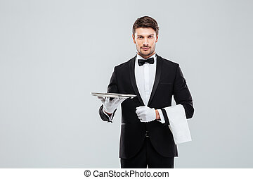 Attractive butler in tuxedo standing and holding silver...