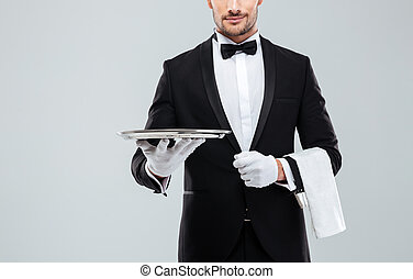 Waiter in tuxedo holding metal empty tray and napkin -...