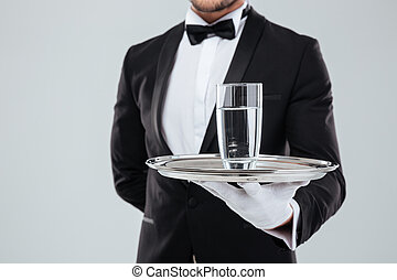 Butler in gloves holding silver tray with glass of water