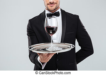Butler in tuxedo holding silver tray with glass of wine