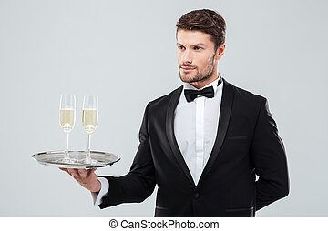 Butler holding silver tray with two glasses of champagne