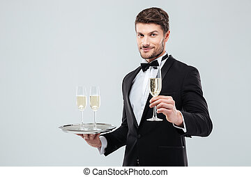Attractive waiter in tuxedo holding tray and glass of...