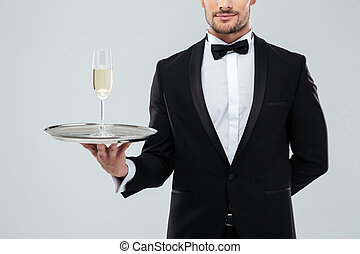 Waiter in tuxedo holding tray with glass of champagne -...