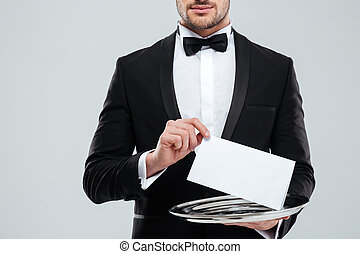 Waiter in tuxedo with bowtie holding blank card on tray -...