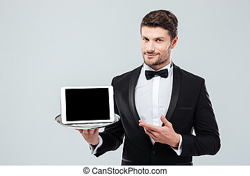 Butler in tuxedo holding and pointing at blank screen tablet...