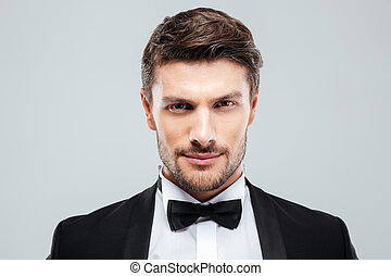 Closeup of attractive confident young man in tuxedo with...