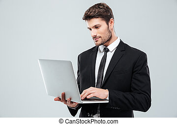 Handsome young businessman standing and using laptop over...