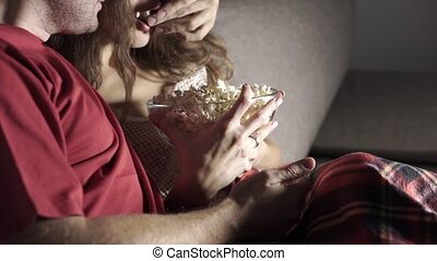 Young couple watching TV and eating popcorn in the evening
