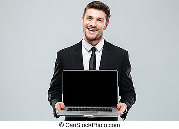 Happy attractive young businessman holding blank screen...