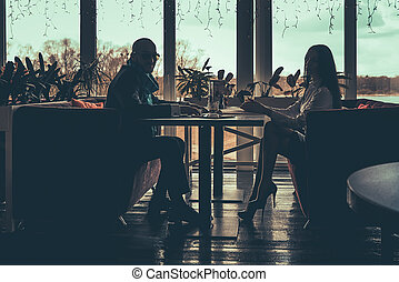 The silhouette of the love couple sitting in cafe