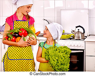 Children little girl cooking vegetables at kitchen -...