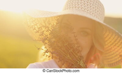 girl in a straw hat and with flowers at sunset