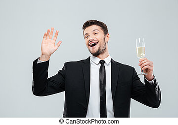 Happy excited young businessman holding glass of champagne...