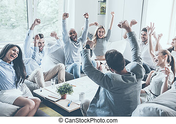 Celebrating success. Group of young business people raising their arms and looking happy while sitting around the desk together