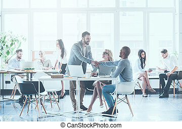 Glad to see you in team! Group of young business people working and communicating with each other in office while two men shaking hands and smiling