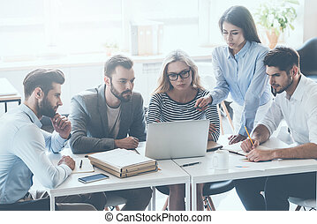 Discussing business issues. Group of young business people sitting at the office desk and discussing something while looking at laptop together