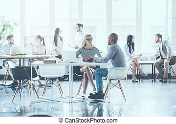 Casual working day. Group of young business people working and communicating with each other while sitting at their working places in office