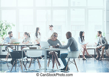 Work in action. Group of young business people working and communicating with each other while sitting at their working places in office