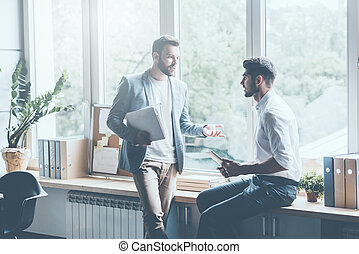 Asking for professional advice Two young businessmen in...