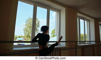 Young beautiful ballerina warming up in ballet class.