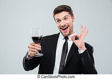 Cheerful drunk businessman drinking red wine and showing ok...