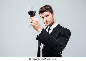 Man sommelier tasting and looking at red wine in glass
