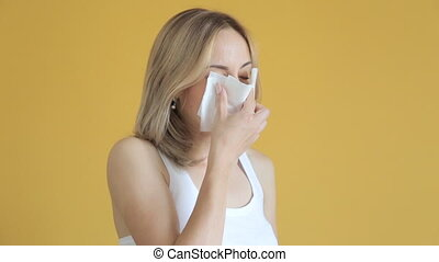 Sick woman in bed blowing nose in paper tissue.