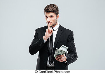 Handsome young businessman holding money and showing silence...