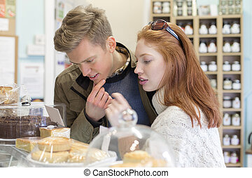 Shall I have chocolate or sponge? - Young couple in a small...