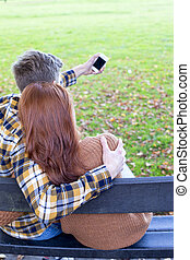 Selfie in the Park - Rear view of a young couple taking a...