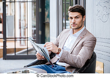 Man in suit sitting at table in cafe outdoors - Attractive...