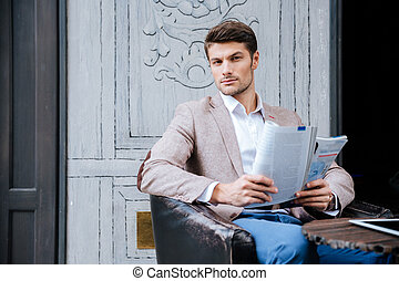 Young businessman reading a newspaper outdoors - Young...