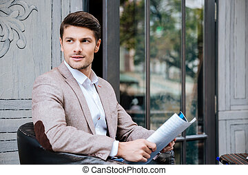 Young handsome businessman reading a newspaper in coffee...