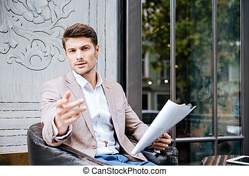 Businessman holding newspaper and pointing at something outdoor